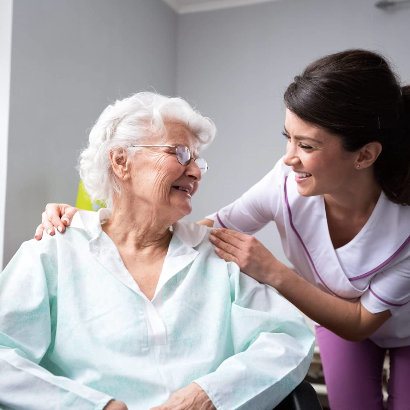 Satisfied and happy senior woman patient with nurse at nursing home