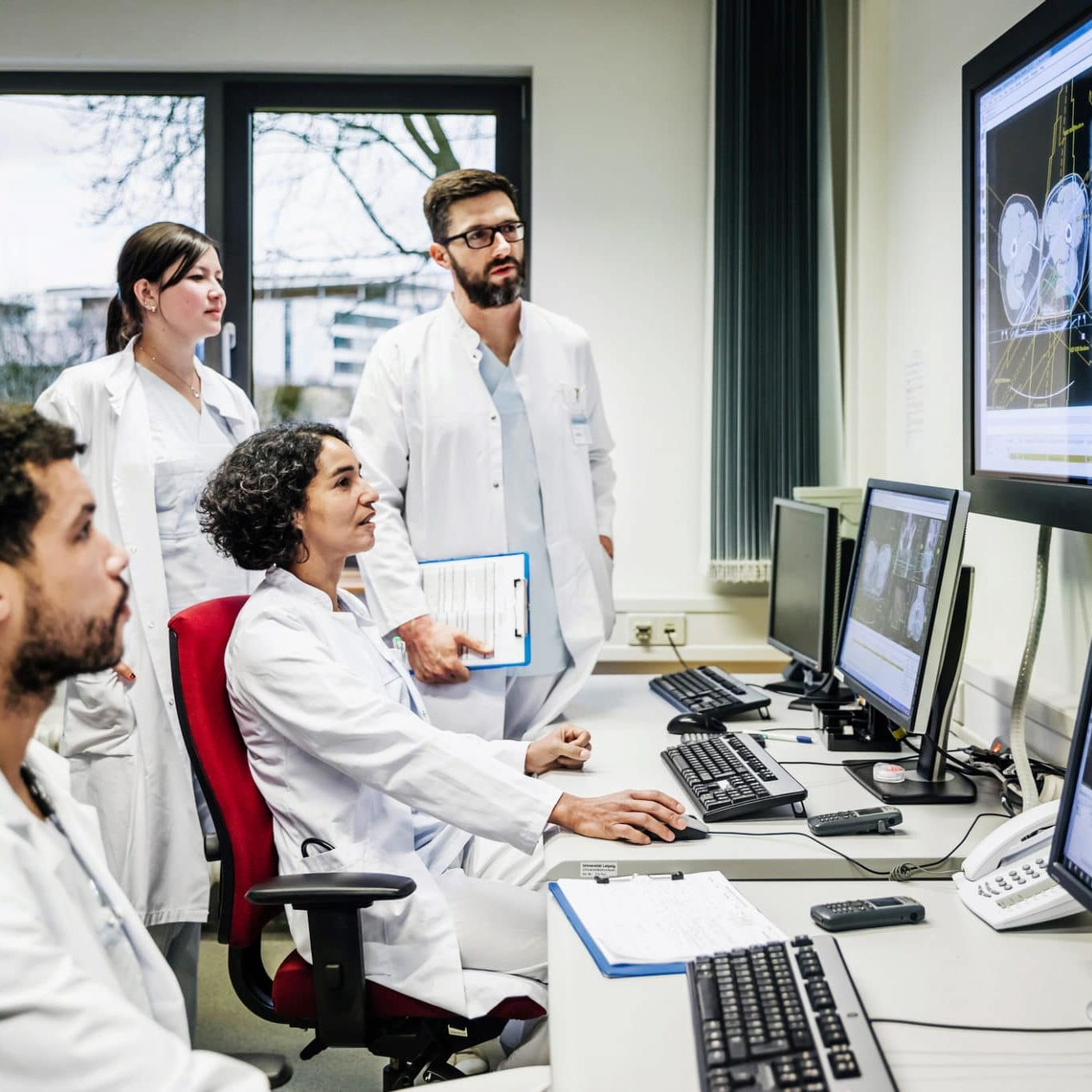 A group of clinical doctors monitoring a patient's condition, looking at information on a computerscreen in a hospital office.